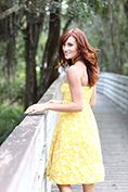 lifestyle model in yellow dress looking back while walking