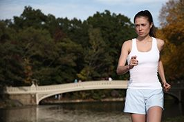 young fitness lifestyle model running along central park lake